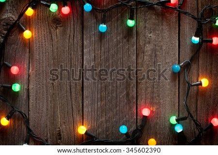 Christmas colorful lights frame on wooden table with copy space - stock photo