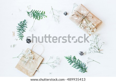 Christmas composition. Christmas gift, pine cones, thuja branches and gypsophila flowers. Flat lay, top view
