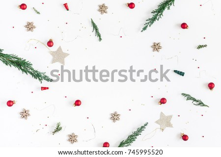 Christmas composition. Frame made of christmas tree branches, golden decorations and red berries on white background. Flat lay, top view, copy space.