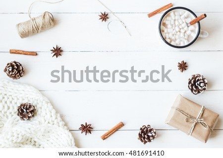 Christmas composition. Hot chocolate, cinnamon sticks, anise star, marshmallow, knitted blanket, christmas gift and cones. Winter concept. Flat lay, top view