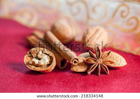 Christmas composition on a red table cloth surface. Almonds, cinnamon sticks, star anise, opened walnut. - stock photo