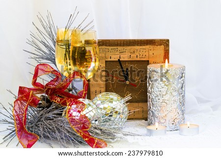 Christmas composition with clock, glasses and a thick silver candle,red bow  and Christmas tree balls - stock photo