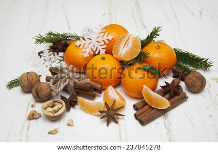 Christmas composition with fresh mandarin oranges, cinnamon, anise, walnuts on old wooden background - stock photo