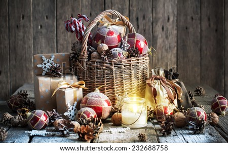 Christmas Composition with Gifts and Burning Candle. Basket, red balls, pine cones, snowflakes on Wooden Table. Vintage style - stock photo