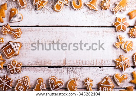 Christmas composition with gingerbreads. Studio shot on white wooden background. - stock photo