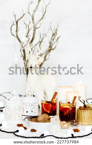Christmas composition with mulled wine, walnuts, candles and white vintage decorations. White deer in background. Shallow dof, selective focus.  - stock photo