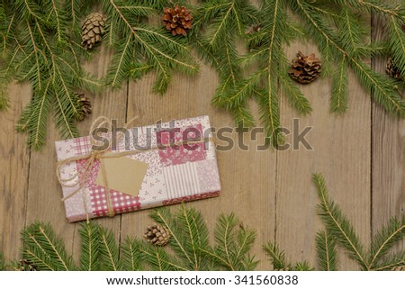 Christmas composition with pink present, fir tree and pine cones on wooden background in vintage style with copyspace - stock photo