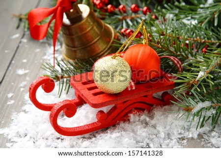 Christmas composition with sleigh, pinecone and bell - stock photo