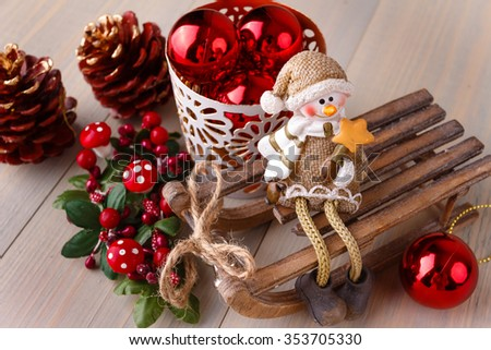 Christmas composition. Xmas and New Years decorations: red balls in white basket, pine cones, elf sitting on wooden sled and little mushrooms on wooden background. Winter holidays card. - stock photo