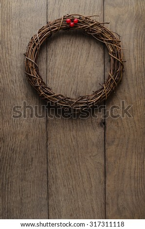 Christmas concept. A simple, natural Christmas wreath woven from soft twigs with artificial red berries, hanging on an old, weathered oak wood plank door. - stock photo