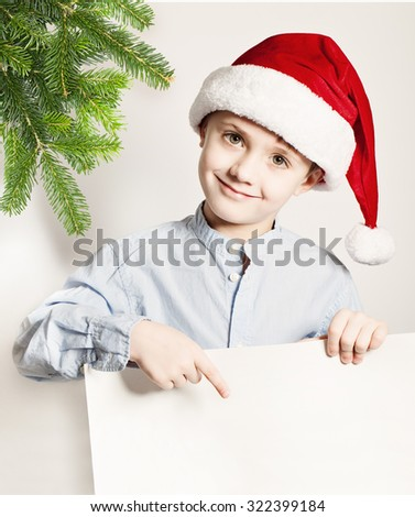 Christmas Concept. Child Boy in Santa Hat Showing White Banner Background. Smiling Little Boy, Xmas Tree Twig and Blank  Paper - stock photo