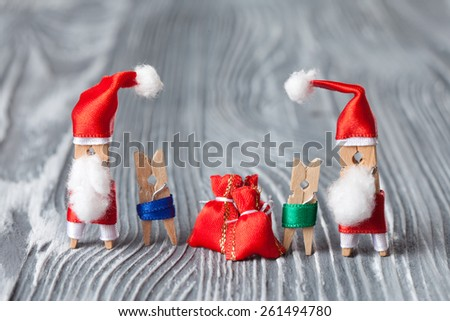 Christmas concept - clothespin. 2 Santa Clauses with kids and gifts. (soft focus, vintage wood background). - stock photo