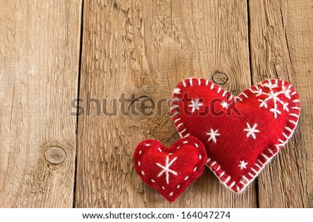 Christmas concept (decoration). Two red handmade hearts over rustic wooden background (texture) close up, horizontal.