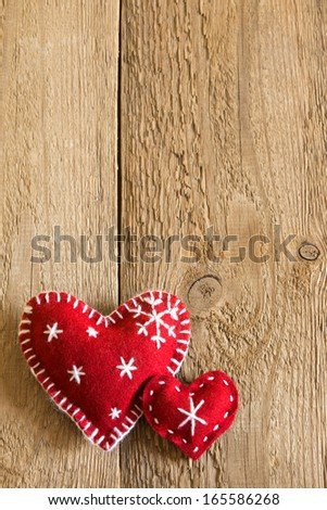 Christmas concept (decoration). Two red handmade hearts over rustic wooden background (texture) close up, vertical, copy space. - stock photo