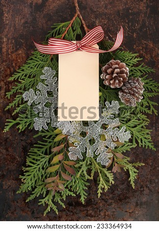 Christmas concept. Fir tree branches, pine cones, snowflakes and red and white bow on brown rustic background, and blank tag. Use your own text. - stock photo