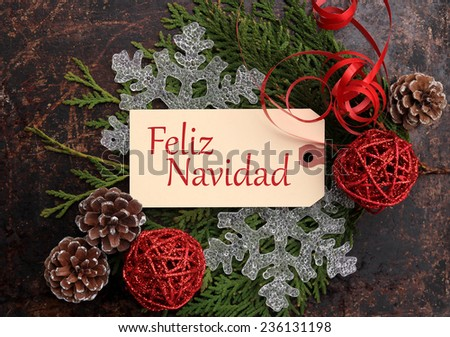 Christmas concept. Fir tree branches, pine cones, snowflakes, red wicker balls and red ribbon on brown rustic background, and tag with the phrase Merry Christmas in Spanish. - stock photo