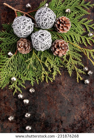 Christmas concept. Fir tree branches, pinecones, silver wicker balls and bells on brown rustic background, with copy space. Use your own text. - stock photo