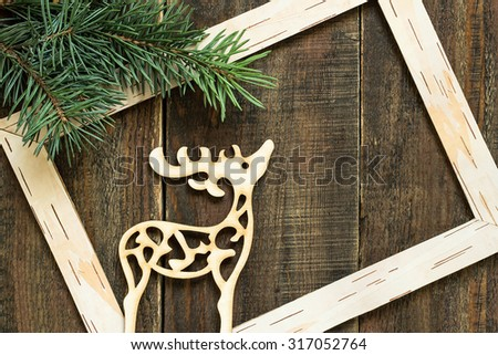 Christmas concept: fresh spruce branches, frame of birch bark and wooden Christmas decoration deer - stock photo
