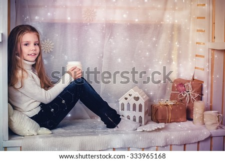 Christmas concept.  Girl with cup of tea in christmas decoration. - stock photo