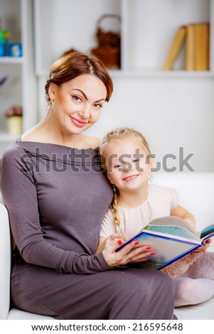 Christmas concept. happy mother and daughter in a room reading a book - stock photo