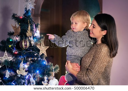 Christmas concept. Little baby boy with mother decorates the Christmas tree. Year-old child waiting New Year 2017, happy family concept