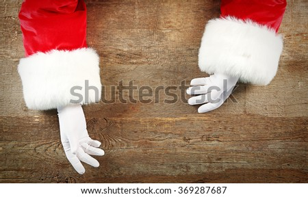 Christmas concept. Santa Claus hands on wooden background