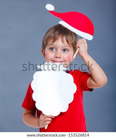 Christmas concept. Smiling funny boy in Santa red hat in studio. - stock photo
