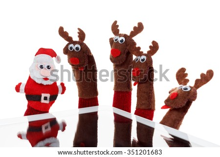 Christmas concept toy Santa Claus and reindeer with a gift in hand touchpad. Isolated on White Background