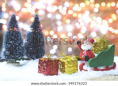 Christmas concept, toy santa sleigh, pine tree and gift boxes on wooden floor and blur green and light bokeh