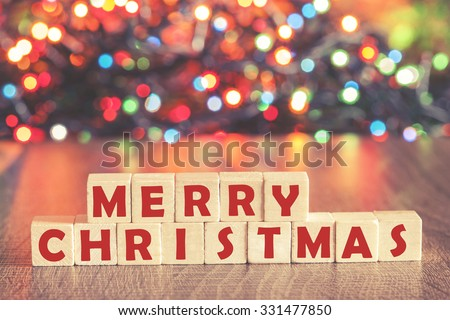 Christmas concept with Merry Christmas wish formed on wooden blocks and defocused bokeh Christmas lights background - stock photo