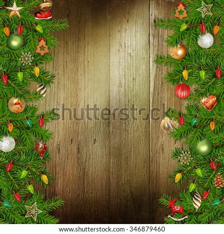Christmas congratulatory background with pine branches and Christmas ornaments on the wooden background