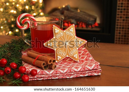 Christmas cookie and hot apple cider by the fireplace. Also available in vertical.  - stock photo