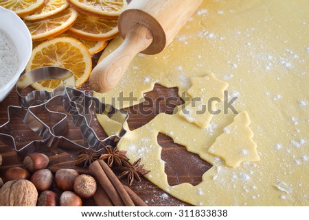 Christmas cookie dough, cookie cutters, spices and nuts - stock photo