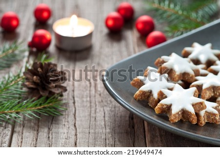 Christmas cookies and candle with festive decoration - stock photo