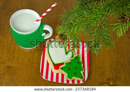 Christmas cookies and milk in mug with sweater under a holiday tree - stock photo