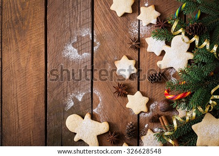Christmas cookies and tinsel on a dark wooden background. Top view - stock photo