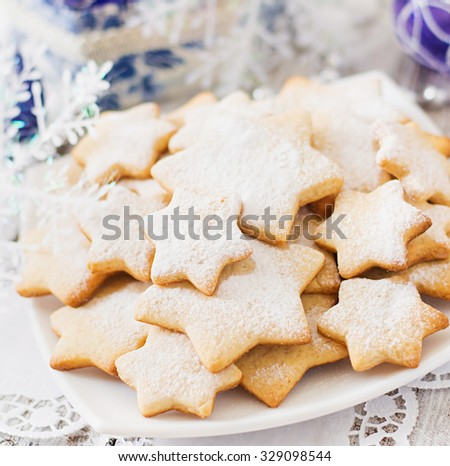 Christmas cookies and tinsel on a light wooden background - stock photo