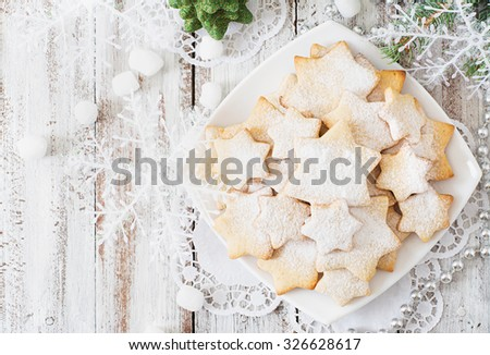 Christmas cookies and tinsel on a light wooden background. Top view