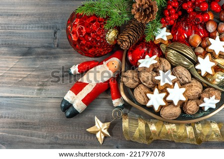 christmas cookies and walnuts with vintage festive decorations on wooden background