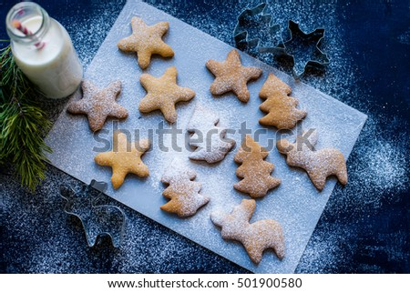 Christmas cookies, cookie cutters, bottle of milk and christmas tree on the blue wooden background