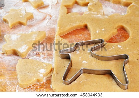 Christmas cookies cutted with forms on the board (bell, christmas tree, deer, star)
