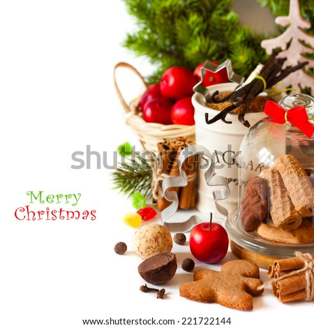 Christmas cookies in a glass bell jar and ingredients for baking on white. - stock photo