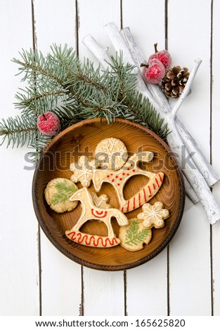 Christmas cookies in festive decor on a in wooden plate, and white rustic table decorated with fir branches - stock photo