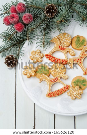 Christmas cookies in festive decor on a white porcelain plate, and white rustic table decorated with fir branches - stock photo