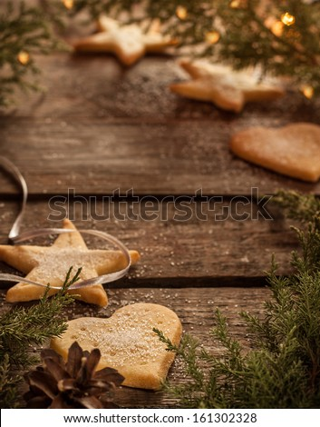 Christmas cookies, pine tree branch and lights on vintage wood - background with text space. - stock photo