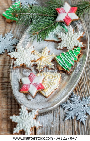 Christmas cookies sprinkled with powdered sugar on a metal tray.