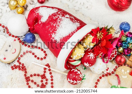 Christmas Cookies. Sweet Sugar  Santa Hat, decorated with festive royal icing and Christmas cookies on festive table. Selective focus - stock photo