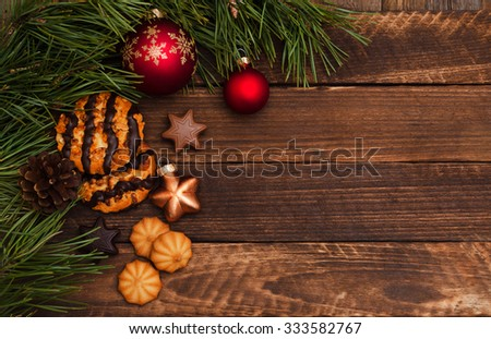 Christmas cookies with fir tree branches, balls and festive decor on the old wood background