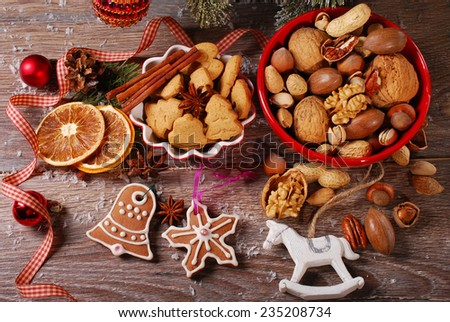 christmas cookies with spices and nuts assortment in red bowls on wooden background - stock photo