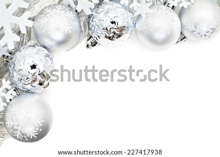 Christmas corner border of snowflakes and silver baubles over a white background            - stock photo
